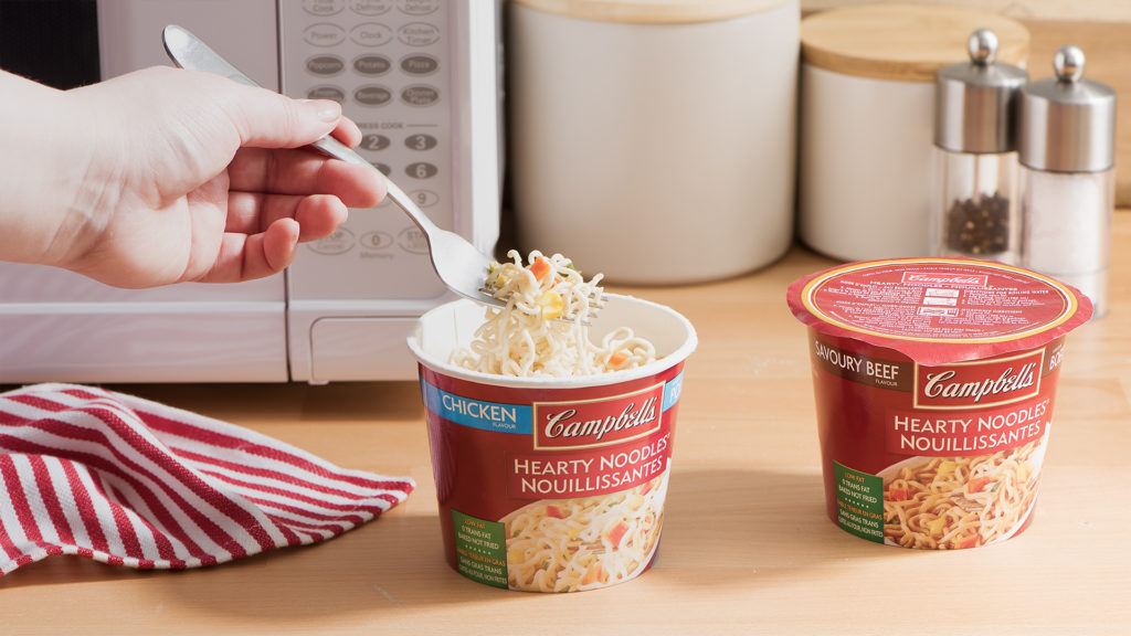 Campbell's hearty noodles beside microwave
